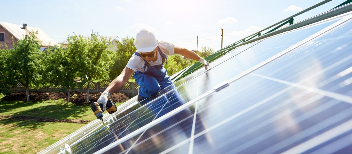 Worker Mounting Solar Panels For Renewable Energy On Houses Roof